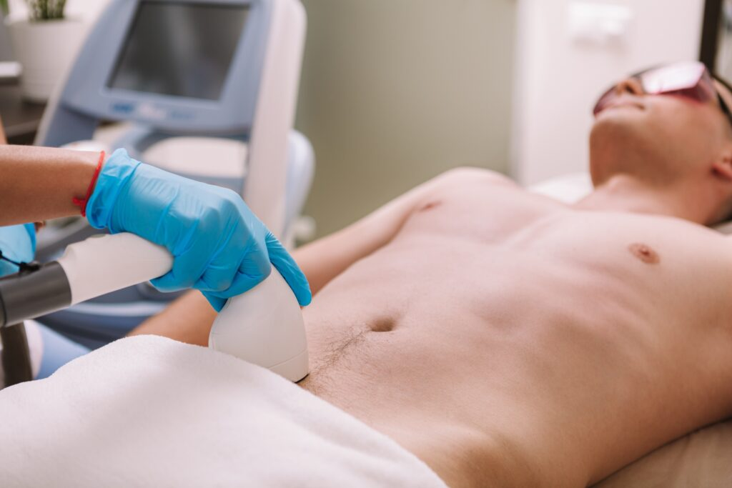 Man getting laser hair removal treatment at beauty clinic