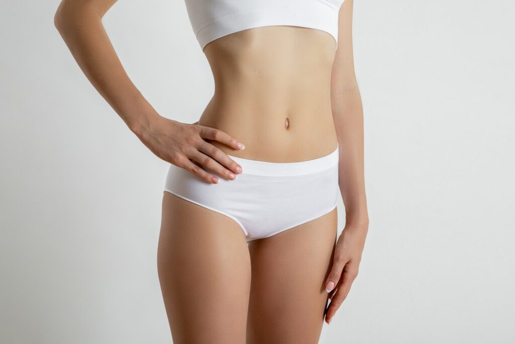 Young slim woman is standing in white underwear
