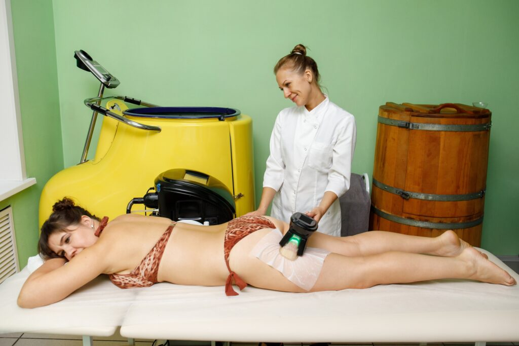 Woman getting cryolipolysis fat treatment on hip in beauty salon