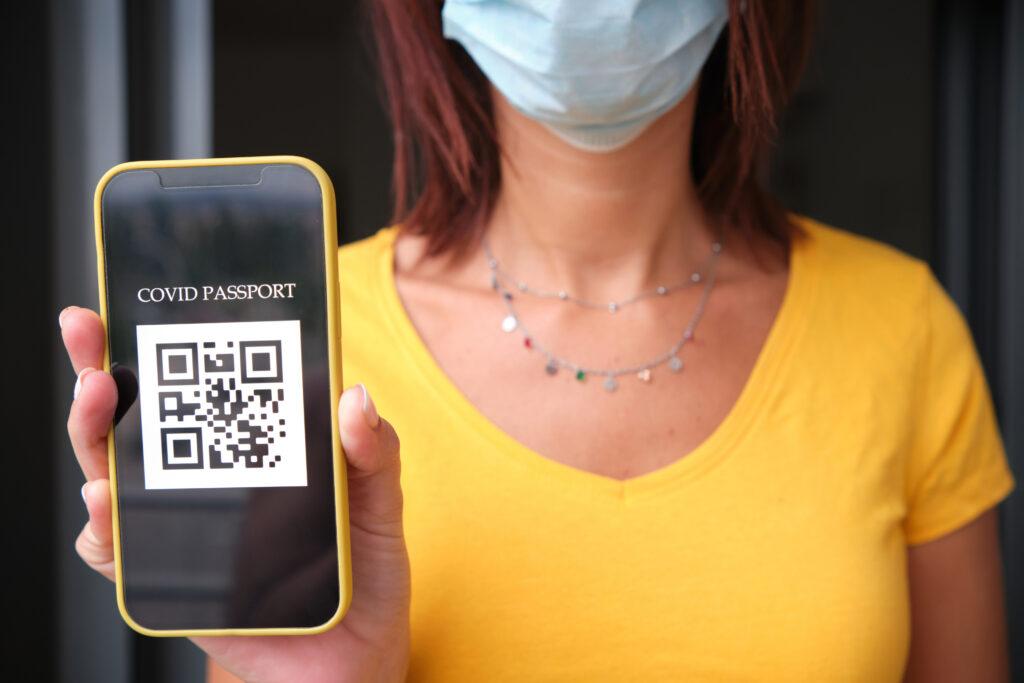 unrecognizable woman with covid passport qr on smartphone - coronavirus pandemic concept