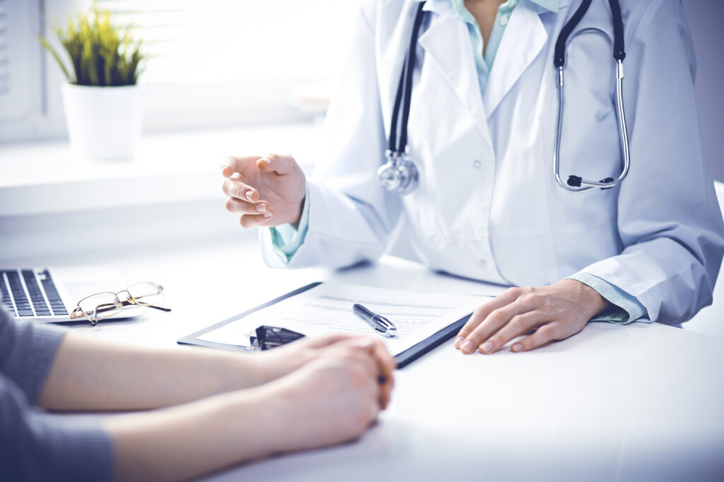 Doctor,And,Female,Patient,Sitting,At,The,Desk,And,Talking